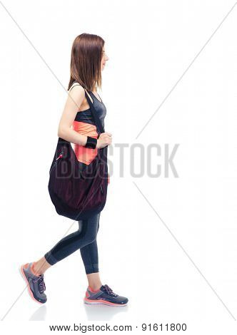 Side view portrait of a fitness woman walking with bag isolated on a white background