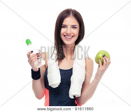 Happy sports woman holding apple and bottle with water isolated on a white background. Looking at camera
