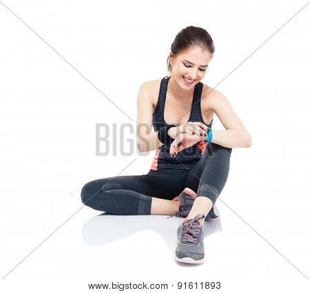 Happy sporty woman sitting on the floor and using smart watch isolated on a white background