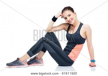 Happy beautiful sports woman sitting on the floor isolated on a white background and looking at camera