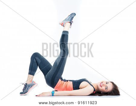 Happy woman lying on the floor and stretching legs isolated on a white background. Looking at camera