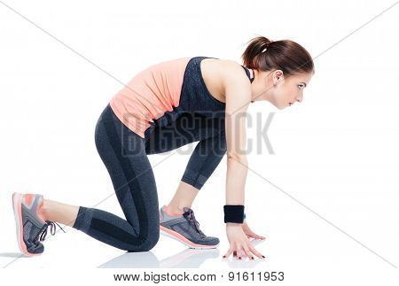 Side view portrait of a runner sporty woman in start position isolated on a white background
