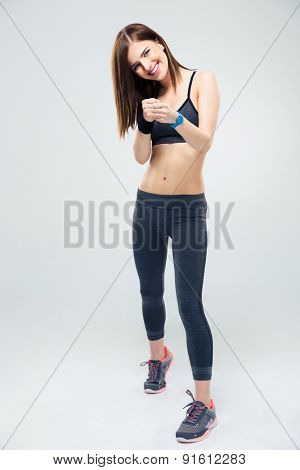 Full length portrait of a happy fitness young woman fighting over gray background