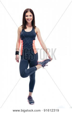 Full length portrait of a smiling sports woman stretching leg isolated on a white background. Looking at cameta