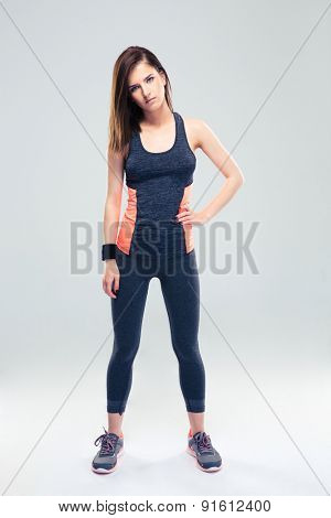 Full length portrait of a beautiful fitness woman standing on gray background and looking at camera
