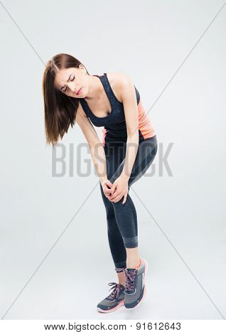 Sports woman having pain in knee over gray background