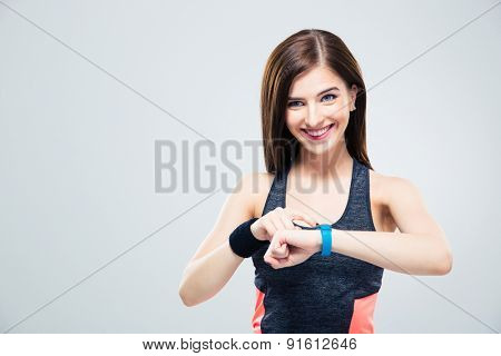 Smiling woman using activity tracker over gray background and looking at camera