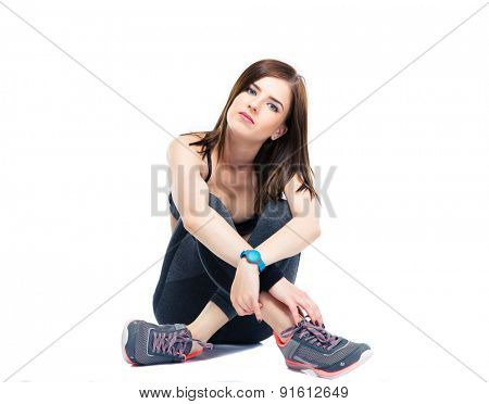 Serious fitness woman resting on the floor isolated on a white background