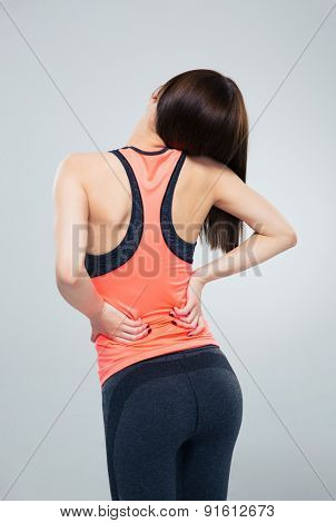 Fitness woman having back pain over gray background
