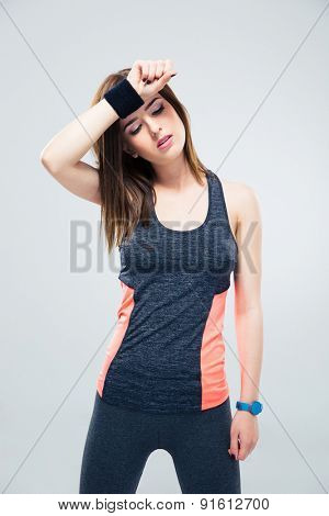 Sports woman wipes the sweat from his brow over gray background