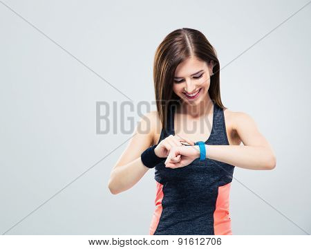 Happy young woman using activity tracker over gray background