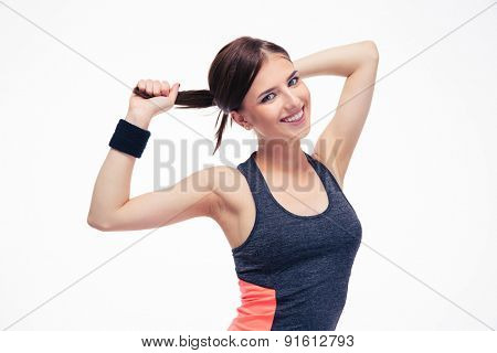 Smiling cute fitness woman holding her hair in ponytail isolated on a white background. Looking at camera