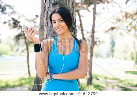Happy sporty woman with headphones holding smartphone outdoors and looking at camera