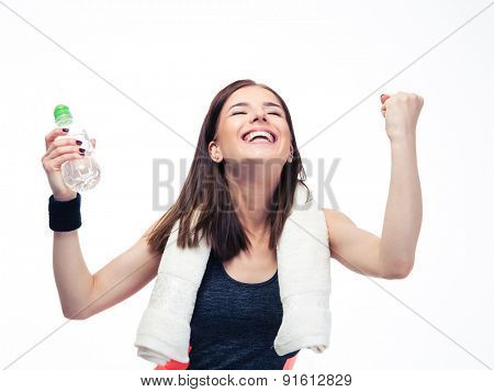 Fitness woman with towel holding bottle with water and celebrating her victory isolated on a white background