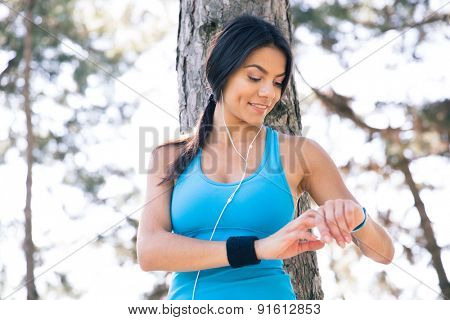 Smiling sporty woman using smart watch outdoors. Leaning on the tree