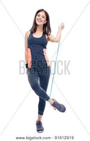 Full length portrait of a happy fitness woman standing with jumping rope isolated on a white background. Looking at camera