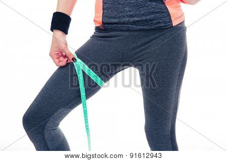 Closeup image of a woman measuring her thigh circumference with tape isolated on a white background
