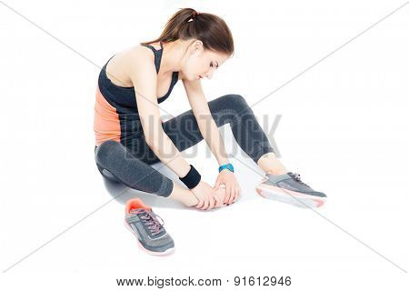 Portrait of a sporty woman with pain on leg isolated on a white background