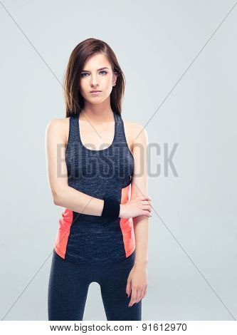 Serious cute fitness woman standing on gray background and looking at camera