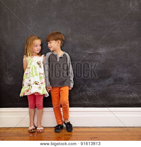 Little Boy And Girl Standing In Front Of Blackboard