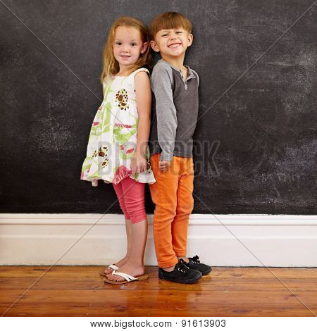 Little Kids Standing In Front Of Blackboard
