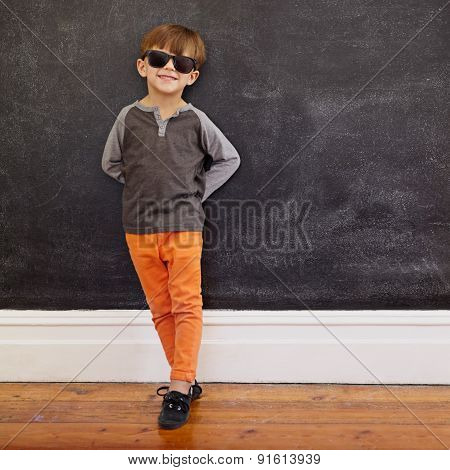 Stylish Little Boy Standing In Front Of The Blackboard