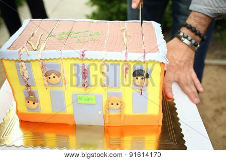 MOSCOW - MAY 28, 2014: Cutting the cake in a shape of the nursery building with windows and children faces at the graduation nursery number 2604 in Moscow
