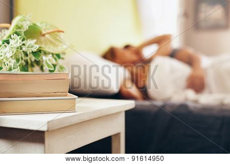 Side Table With Books And Flowers In Bedroom