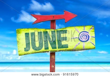 June direction sign with beach background