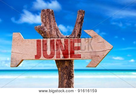 June wooden sign with beach background