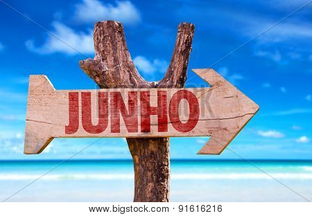 June (in Portuguese) wooden sign with beach background