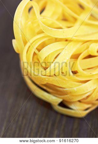 Tagliatelle italian pasta on wood background