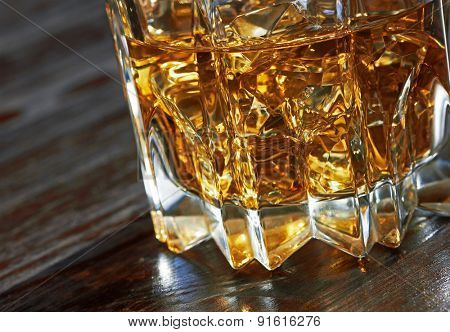 Whiskey in glasses on wooden table, close-up