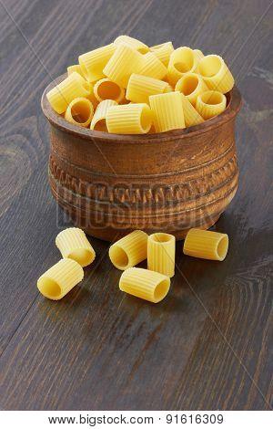 Rigatoni italian pasta in wood bowl, on wood background