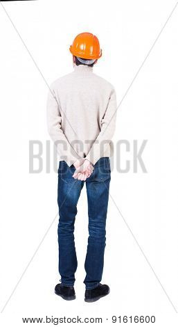 Backview of an engineer in construction helmet stands.  Rear view people collection.  backside view of person.  Isolated over white background. Engineer hands clasped behind his back facing forward.