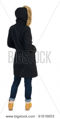 Back view woman in winter jacket  looking up.    Isolated over white background. Girl in a black winter jacket with a hood looking to the right with his hands in his pockets.