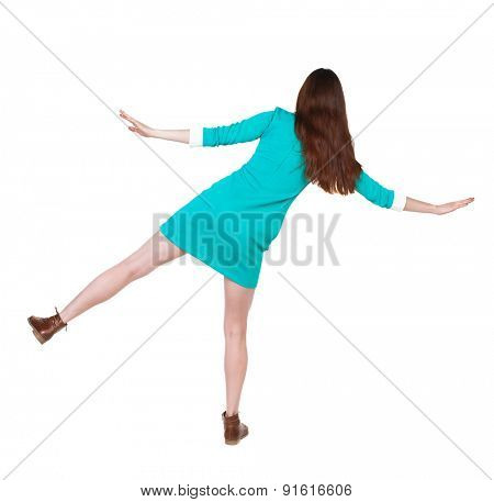 Back view woman Balances waving his arms.    backside view of person.  Isolated over white background. The girl in a blue dress with brown shoes keeps the balance standing on one leg.