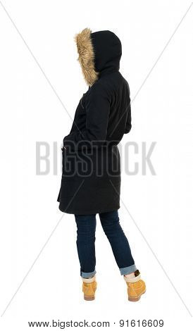 Back view woman in winter jacket  looking up.  Isolated over white background. Girl in a black winter jacket with a hood looking to the left with his hands in his pockets.