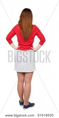 back view standing young beautiful  woman in dress. girl  watching. Rear view people collection. backside view person. Isolated over white background. Girl in white skirt standing with hands on waist