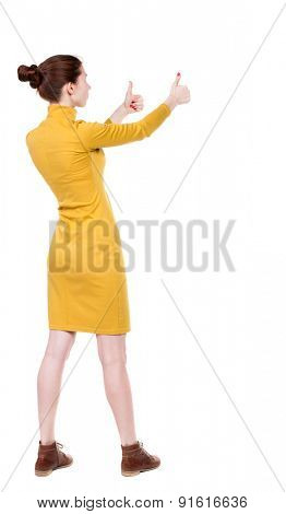 Back view of  woman thumbs up. Rear view people collection. backside view of person. Isolated over white background. Girl in mustard strict dress stands sideways and two hands showing thumb.