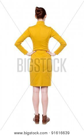 back view of standing young beautiful  woman.   Rear view people collection.  backside view of person.  Isolated over white background. Girl in mustard strict dress standing with hands on hips.