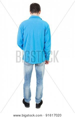 Back view of man in jeans. Standing young guy. Rear view people collection.  backside view of person.  Isolated over white background. The guy in the blue sweater looks down at his feet.