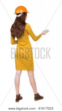 Backview of business woman in construction helmet stands and enjoys tablet or using a mobile phone.  backside view of person. Girl engineer in the yellow dress holds someone plate.