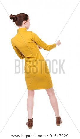 back view of standing woman pulling a rope from the top or cling to something.  .  Isolated over white background. Girl in a dress with a simple mustard hair tied in a bun pulling a rope to the right