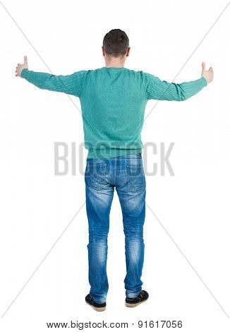 Back view of man in jeans. Standing young guy. Rear view people collection.  backside view of person.  Isolated over white background. The guy tries to put her arms around something big.