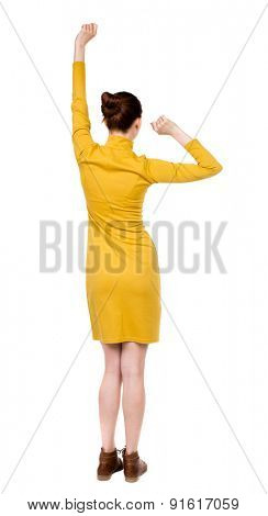 back view of dancing young beautiful  woman in dress. Rear view people collection.  backside view of person.  Isolated over white background. Girl in mustard strict dress enjoys swinging fists.
