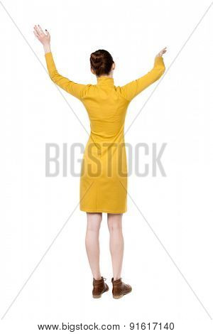 back view of dancing young beautiful  woman in dress. Rear view people collection.  backside view of person.  Isolated over white background. Girl in mustard strict dress dancing waving his arms.