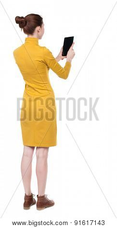 back view standing young beautiful  girl with tablet computer in hands. girl  watching.  backside view of person.  Isolated over white background. Girl in mustard strict dress looks into  tablet.