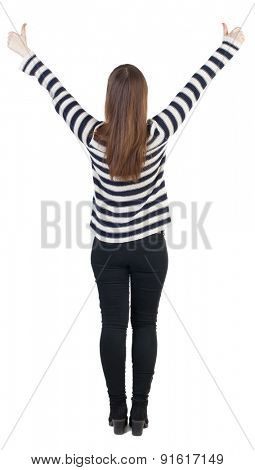 Back view of  woman thumbs up. Rear view people collection. backside view of person.slender blonde in a jeans shows the symbol of success or hitchhiking. With both hands, hand girl shows thumbs.