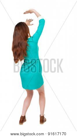 back view woman in dress protects hands from what is falling from above. Rear  backside view.  Isolated over white background. girl in blue dress with brown boots close hands against danger from above